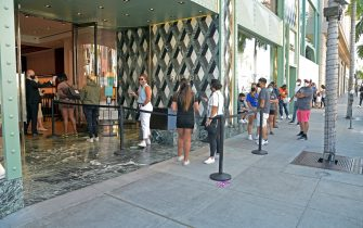 LOS ANGELES, CALIFORNIA - JUNE 30: People practice social distancing while waiting in line at luxury retailer Gucci on June 30, 2020 in Beverly Hills, California. The state has been hit with a large spike in coronavirus cases, which may bring about lockdown conditions once again. (Photo by Michael Tullberg/Getty Images)