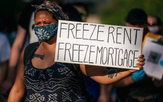 MINNEAPOLIS, MN - JUNE 30: A woman holds a sign up as demonstrators march in the street during the Cancel Rent and Mortgages rally on June 30, 2020 in Minneapolis, Minnesota. The rally was organized to demand the temporary cancellation of rents and mortgages as COVID-19 continues to adversely effect the economy. (Photo by Brandon Bell/Getty Images)
