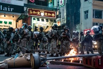 HONG KONG, CHINA - JULY 01: Riot police secure an area in front of a burning road block during a demonstration against the new national security law on July 1, 2020 in Hong Kong, China. Hong Kong marks the 23rd anniversary of its handover to China on July 1 after Beijing imposed the new national security law. (Photo by Anthony Kwan/Getty Images)
