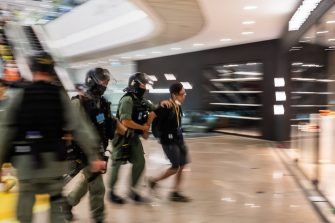 HONG KONG, CHINA - JULY 01: Riot police stop and search a demonstrator during a rally against a new national security law, on the 23rd anniversary of the city's handover from Britain to China on July 1, 2020 in Hong Kong, China. (Photo by Billy H.C. Kwok/Getty Images)