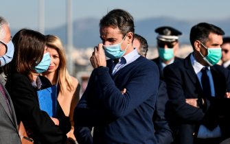 "Greek Prime Minister Kyriakos Mitsotakis (C) wearing a protective face mask, arrives to attend the departure of minor migrants who were living in camps on the Greek islands, at the International Airport of Athens, to travel on a special flight to Germany, on April 18, 2020. - Forty-nine minors have taken a flight to Germany as Greece's migration minister on April 14 said dozens of unaccompanied migrant children would be relocated to other EU countries as a rights group described Athens' detention conditions for minors as ""abusive"". (Photo by ARIS MESSINIS / AFP) (Photo by ARIS MESSINIS/AFP via Getty Images)"