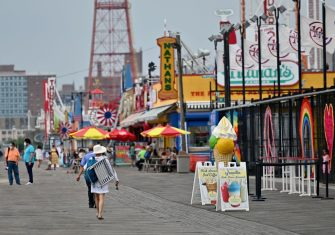 Poeple walk at Coney Island boardwalk on July 1, 2020 in New York City, as beaches reopen to the public for swimming. - Hospitalizations and infections continue to hit new lows but officials fear a spike in rates elsewhere could cause an uptick in New York as it slowly reopens business and other activities. (Photo by Angela Weiss / AFP) (Photo by ANGELA WEISS/AFP via Getty Images)