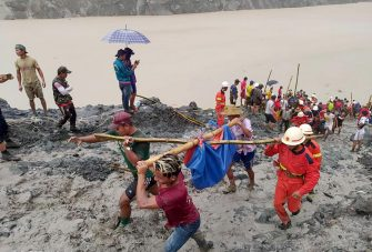 epa08522225 A handout photo made available by the Myanmar Fire Services Department shows rescue workers carrying the body of a victim after a landslide accident at a jade mining site in Hpakant, Kachin State, Myanmar, 02 July 2020. According media reports, search and rescue efforts are ongoing after a landslide was triggered by heavy rain in the area.  EPA/Myanmar Fire Services Department HANDOUT  HANDOUT EDITORIAL USE ONLY/NO SALES