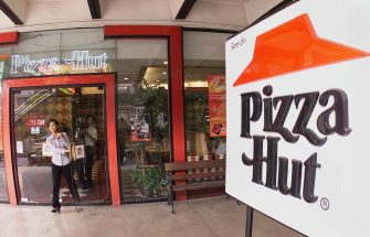 BANGKOK, THAILAND:  A customer walks out of a Pizza Hut restaurant 20 January 2000 at a Bangkok branch of the US food franchise.  Thailand's Pizza Plc. said it would give up rights to the Pizza Hut chain of restaurants after 20 years following a breakdown of talks with the US franchise holder and would rebrand its 116 pizza parlours in the country.     (ELECTRONIC IMAGE) AFP PHOTO/Pornchai KITTIWONGSAKUL (Photo credit should read PORNCHAI KITTIWONGSAKUL/AFP via Getty Images)