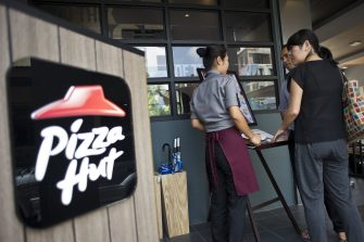 A staff member attends to customers browsing the menu of Pizza Hut's first restaurant in Yangon on October 22, 2015. Pizza Hut is to open its first restaurant in Yangon, the latest major western fast food chain to enter the emerging nation where consumer habits are changing fast. AFP PHOTO / Ye Aung THU / AFP PHOTO / Ye Aung Thu        (Photo credit should read YE AUNG THU/AFP via Getty Images)