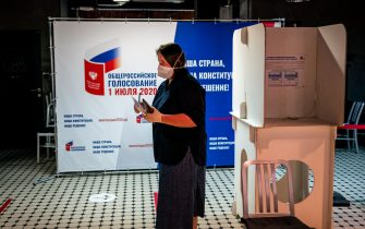 A woman wearing a face mask and gloves - a measure against the spread of the coronavirus disease - prepares to cast her ballot in a nationwide vote on constitutional reforms at a polling station inside the GULAG History Museum in Moscow on July 1, 2020. (Photo by Dimitar DILKOFF / AFP) (Photo by DIMITAR DILKOFF/AFP via Getty Images)