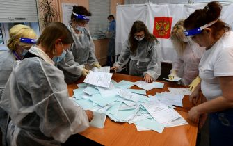 Members of a local electoral commission wearing protective gear - a measure against the spread of the coronavirus disease - count votes in a nationwide ballot on constitutional reforms at a polling station in the far eastern city of Vladivostok on July 1, 2020. (Photo by Pavel KOROLYOV / AFP) (Photo by PAVEL KOROLYOV/AFP via Getty Images)