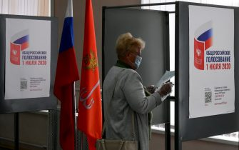 A woman wearing a face mask and gloves - a measure against the spread of the coronavirus disease - prepares to cast her ballot in a nationwide vote on constitutional reforms at a polling station in Saint Petersburg on July 1, 2020. (Photo by OLGA MALTSEVA / AFP) (Photo by OLGA MALTSEVA/AFP via Getty Images)