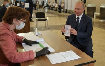TOPSHOT - Russian President Vladimir Putin shows his passport to a member of a local electoral commission as he arrives to cast his ballot in a nationwide vote on constitutional reforms at a polling station in Moscow on July 1, 2020. (Photo by Alexei Druzhinin / SPUTNIK / AFP) (Photo by ALEXEI DRUZHININ/SPUTNIK/AFP via Getty Images)