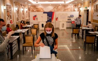 A woman wearing a face mask - a measure against the spread of the coronavirus disease - casts her ballot in a nationwide vote on constitutional reforms at a polling station in Moscow on July 1, 2020. (Photo by Dimitar DILKOFF / AFP) (Photo by DIMITAR DILKOFF/AFP via Getty Images)