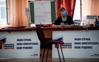 A member of a local electoral commission wearing a face mask waits for voters during the early vote in a nationwide constitutional referendum that could extend President Vladimir Putin's term in the Kremlin, at a polling station in Moscow on June 29, 2020. - Election officials opened polls ahead of the official July 1 vote to avoid overcrowding that could spread coronavirus infections. Russian state pollster VCIOM on June 29, 2020 published an exit poll showing a vast majority of Russians backing proposed constitutional reforms, days before the end of voting. (Photo by Alexander NEMENOV / AFP) (Photo by ALEXANDER NEMENOV/AFP via Getty Images)