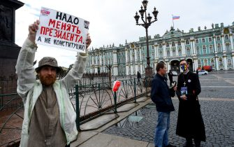 """A man holds a placard reading """"Need to change the president but not the Constitution"""" as he protests against amendments to the Constitution of Russia on Dvortsovaya Square in downtown Saint Petersburg on July 1, 2020, as Russians vote in the final day of a ballot on constitutional reforms allowing President Putin to potentially stay in power until 2036. (Photo by OLGA MALTSEVA / AFP) (Photo by OLGA MALTSEVA/AFP via Getty Images)"""