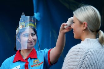 SYDNEY, AUSTRALIA - JULY 03: Luna Park staff member Ida Ghalandari takes the temperature of guests on arrival to the fun park on July 03, 2020 in Sydney, Australia. Sydney's Luna Park has reopened to the public following its temporary closure on Monday 23 March in response to the COVID-19 pandemic. Restrictions on entertainment venues, weddings, community sport and other gatherings have been eased across NSW since 1 July, but strict physical distancing measures remain in place. (Photo by Lisa Maree Williams/Getty Images)