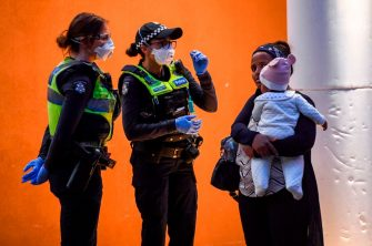 Police speak to residents outside one of nine public housing estates which have been locked down in Melbourne on July 4, 2020 with more than 3000 residents in 1,345 units required to stay home due to an outbreak of the COVID-19 coronavirus. - The Australian state of Victoria recorded its second-highest daily increase in coronavirus cases, with 108 people diagnosed with the virus. (Photo by William WEST / AFP) (Photo by WILLIAM WEST/AFP via Getty Images)