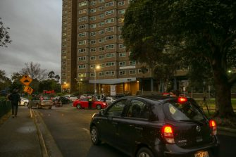 MELBOURNE, AUSTRALIA - JULY 04: Cars entering the housing commission flats in the suburb of Flemington, where a coronavirus outbreak has been recorded, on July 04, 2020 in Melbourne, Australia. Lockdowns across Melbourne are in effect for residents of suburbs identified as COVID-19 hotspots following a spike in new coronavirus cases through community transmission. Residents of the 10 Melbourne hotspot postcodes are only able to leave home for exercise or work, to buy essential items including food or to access childcare and healthcare. Businesses and facilities in these lockdown areas are also restricted and cafes and restaurants can only open for takeaway and delivery. The restrictions will remain in place until at least 29 July.  (Photo by Asanka Ratnayake/Getty Images)