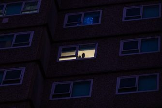 MELBOURNE, AUSTRALIA - JULY 04: A resident at the housing commission flats in the suburb of Flemington looks out of their window where a outbreak has been recorded on July 04, 2020 in Melbourne, Australia. Lockdowns across Melbourne are in effect for residents of suburbs identified as COVID-19 hotspots following a spike in new coronavirus cases through community transmission. Residents of the 10 Melbourne hotspot postcodes are only able to leave home for exercise or work, to buy essential items including food or to access childcare and healthcare. Businesses and facilities in these lockdown areas are also restricted and cafes and restaurants can only open for takeaway and delivery. The restrictions will remain in place until at least 29 July.  (Photo by Asanka Ratnayake/Getty Images)