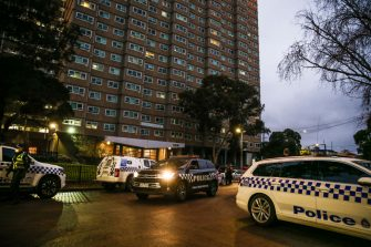 MELBOURNE, AUSTRALIA - JULY 04: Police cars surround the housing commission flats in the suburb of Flemington, where a coronavirus outbreak has been recorded, on July 04, 2020 in Melbourne, Australia. Lockdowns across Melbourne are in effect for residents of suburbs identified as COVID-19 hotspots following a spike in new coronavirus cases through community transmission. Residents of the 10 Melbourne hotspot postcodes are only able to leave home for exercise or work, to buy essential items including food or to access childcare and healthcare. Businesses and facilities in these lockdown areas are also restricted and cafes and restaurants can only open for takeaway and delivery. The restrictions will remain in place until at least 29 July.  (Photo by Asanka Ratnayake/Getty Images)