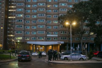 MELBOURNE, AUSTRALIA - JULY 04: Police stand at the front of the housing commission flats in the suburb of Flemington, where a coronavirus outbreak has been recorded, on July 04, 2020 in Melbourne, Australia. Lockdowns across Melbourne are in effect for residents of suburbs identified as COVID-19 hotspots following a spike in new coronavirus cases through community transmission. Residents of the 10 Melbourne hotspot postcodes are only able to leave home for exercise or work, to buy essential items including food or to access childcare and healthcare. Businesses and facilities in these lockdown areas are also restricted and cafes and restaurants can only open for takeaway and delivery. The restrictions will remain in place until at least 29 July.  (Photo by Asanka Ratnayake/Getty Images)