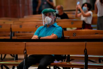 A man wearing a face mask sits at the Sagrada Familia basilica in Barcelona on July 4, 2020 as it reopens with a tribute to healthcare workers following a national lockdown to stop the spread of the novel coronavirus. (Photo by Josep LAGO / AFP) (Photo by JOSEP LAGO/AFP via Getty Images)