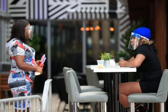 MIAMI BEACH, FLORIDA - JULY 03: Two women wearing face masks speak at a table in The Palace restaurant on July 03, 2020 in Miami Beach, Florida. In order to prevent the spread of COVID-19, Miami-Dade county has closed beaches from July 3-7 and imposed a curfew from from 10pm to 6am. (Photo by Cliff Hawkins/Getty Images)