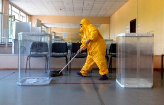 TOPSHOT - An employee disinfects the floor at a polling station in Moscow on June 25, 2020. - Russians were casting early ballots on June 25, 2020 in a nationwide vote on constitutional reforms that could see President Vladimir Putin remain in power until 2036. Election officials opened polling stations in the lead-up to the official voting day on July 1 to reduce the risk of overcrowding that could spread coronavirus infections. (Photo by Yuri KADOBNOV / AFP) (Photo by YURI KADOBNOV/AFP via Getty Images)
