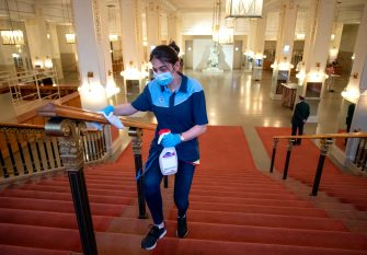 "A woman disinfects a hand rail of a stairway between concerts at the 'Wiener Konzerthaus' in Vienna, Austria on June 6, 2020. - Concert houses in Vienna reopened their doors this weekend for limited audiences after being completely closed due to the new coronavirus lockdown"" (Photo by JOE KLAMAR / AFP) (Photo by JOE KLAMAR/AFP via Getty Images)"