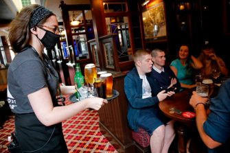 A member of bar staff wearing PPE (personal protective equipment) in the form of a face mask, serves seated customers drinks inside the Wetherspoon pub, Goldengrove in Stratford in east London on July 4, 2020, as restrictions are further eased during the novel coronavirus COVID-19 pandemic. - Pubs in England reopen on Saturday for the first time since late March, bringing cheer to drinkers and the industry but fears of public disorder and fresh coronavirus cases. (Photo by Tolga AKMEN / AFP) (Photo by TOLGA AKMEN/AFP via Getty Images)