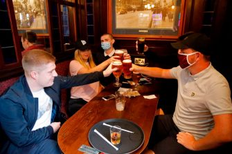 People, some wearing protective face coverings make a toast inside the Wetherspoon pub, Goldengrove in Stratford in east London on July 4, 2020, as restrictions are further eased during the novel coronavirus COVID-19 pandemic. - Pubs in England reopen on Saturday for the first time since late March, bringing cheer to drinkers and the industry but fears of public disorder and fresh coronavirus cases. (Photo by Tolga AKMEN / AFP) (Photo by TOLGA AKMEN/AFP via Getty Images)