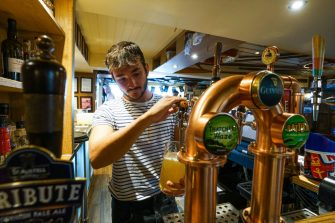 FALMOUTH, ENGLAND - JULY 4:  A member of the bar staff pulls a pint at the Chain Locker pub as it reopens for business on July 4, 2020 in Falmouth, Cornwall, United Kingdom. The UK Government announced that Pubs, Hotels and Restaurants can open from Saturday, July 4th providing they follow guidelines on social distancing and sanitising. (Photo by Hugh R Hastings/Getty Images)