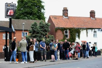 NORWICH, ENGLAND - JULY 04: Customers queue outside the Fat Cat Brewery Tap pub on July 04, 2020 in Norwich, United Kingdom. The UK Government announced that Pubs, Hotels and Restaurants can open from Saturday, July 4th providing they follow guidelines on social distancing and sanitising. (Photo by Stephen Pond/Getty Images)