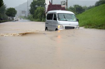 epa08525871 A minivan drives through a flooded street in Yatsushiro, Kumamoto prefecture, southwestern Japan, 04 July 2020. Local authorities asked the evacuation of more than 76,000 residents in Japan's southwestern prefectures of Kumamoto and Kagoshima following floods and mudslides triggered by torrential rain.  EPA/JIJI PRESS JAPAN OUT EDITORIAL USE ONLY/  NO ARCHIVES
