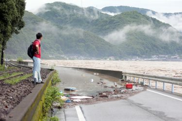 epa08525910 A man looks at the river Kuma overflowing in Yatsushiro, Kumamoto prefecture, southwestern Japan, 04 July 2020. Local authorities asked the evacuation of more than 200,000 residents in Japan's southwestern prefectures of Kumamoto and Kagoshima following floods and mudslides triggered by torrential rain.  EPA/JIJI PRESS JAPAN OUT EDITORIAL USE ONLY/  NO ARCHIVES