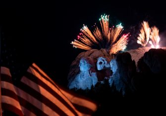 A US flag flies as fireworks explode above the Mount Rushmore National Monument during an Independence Day event attended by the US president in Keystone, South Dakota, July 3, 2020. (Photo by ANDREW CABALLERO-REYNOLDS / AFP) (Photo by ANDREW CABALLERO-REYNOLDS/AFP via Getty Images)