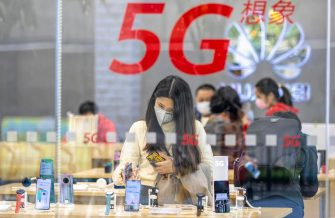 A woman wearing a face mask looks at smartphones in a Huawei shop in Guangzhou, Guangdong, China, 21 February 2020. ANSA/ALEX PLAVEVSKI