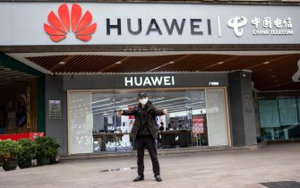 A man wearing a protection mask for coronavirus stretches in front of Huawei store in Guangzhou, Guangdong Province, China, 05 February 2020. ANSA/ALEX PLAVEVSKI
