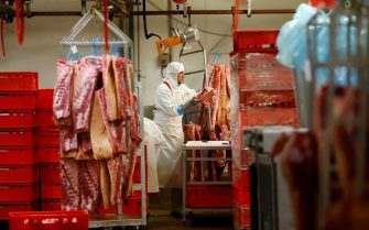 An employee handles meat at the AIM (Abattoirs industriels de la Manche) slaughterhouse in Sainte-Cécile, northwestern France, on July 5, 2018, two days before their last day of work on July 7. - The 237 employees of the AIM Group slaughterhouse in Normandy, who were counting on a takeover of their company by five Breton breeders, saw July 4, 2018 their hopes shattered after the withdrawal at the last minute of the only offer of redemption. (Photo by CHARLY TRIBALLEAU / AFP)        (Photo credit should read CHARLY TRIBALLEAU/AFP via Getty Images)