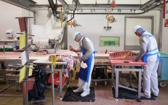 Workers cut pieces of beef in the SCAVO meat processing plant in Cholet, western France, on September 9, 2014. AFP PHOTO / JEAN-SEBASTIEN EVRARD