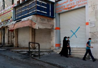 Youths clad in face masks walk past closed shops in the centre of the flashpoint city of Hebron in the occupied West Bank on July 2, 2020, after authorities re-imposed COVID-19 coronavirus pandemic lockdown measures due to a recent spike in cases. (Photo by HAZEM BADER / AFP) (Photo by HAZEM BADER/AFP via Getty Images)