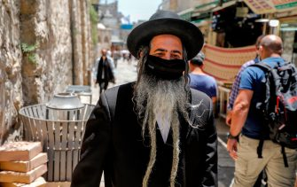 An Ultra-Orthodox Jewish man, wearing a protective facemask, walks in Jerusalem's Old City on July 3, 2020, during the novel coronavirus pandemic. (Photo by AHMAD GHARABLI / AFP) (Photo by AHMAD GHARABLI/AFP via Getty Images)