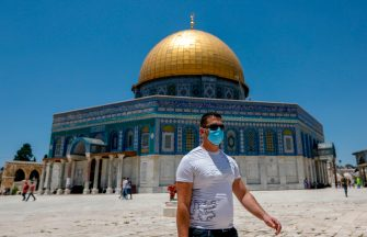 A Palestinian man, wearing a protective facemask, walks in front of the Dome of the Rock Mosque, in Jerusalem's Al-Aqsa mosques compound on July 3, 2020, during the novel coronavirus pandemic. (Photo by AHMAD GHARABLI / AFP) (Photo by AHMAD GHARABLI/AFP via Getty Images)