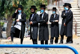 Ultra-Orthodox Jews, wearing protective masks due to the COVID-19 pandemic, gather at the entrance of a neighbourhood that has been isolated following a recent increase in coronavirus cases in the southern coastal city of Ashdod, on July 2, 2020. (Photo by JACK GUEZ / AFP) (Photo by JACK GUEZ/AFP via Getty Images)