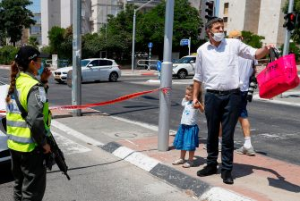 Israeli security forces, wearing protective masks due to the COVID-19 pandemic, control access to a neighbourhood that has been isolated following a recent increase in coronavirus cases in the southern coastal city of Ashdod, on July 2, 2020. (Photo by JACK GUEZ / AFP) (Photo by JACK GUEZ/AFP via Getty Images)