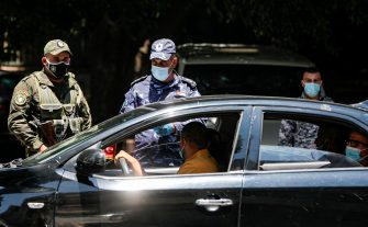 Mask-clad members of the Palestinian Authority's security forces stop vehicles at a checkpoint in the city of Nablus in the occupied West Bank on July 2, 2020, after authorities re-imposed COVID-19 coronavirus pandemic lockdown measures due to a recent spike in cases. (Photo by JAAFAR ASHTIYEH / AFP) (Photo by JAAFAR ASHTIYEH/AFP via Getty Images)