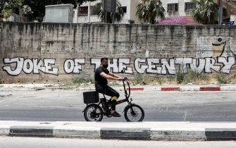 """A mask-clad man walks/rides an electric bicycle along a street past a mural drawn on a wall reading """"Joke of the Century"""" (referring to US President Donald Trump's proposed Israeli-Palestinian peace plan) in the city of Nablus in the occupied West Bank on July 2, 2020, after authorities re-imposed COVID-19 coronavirus pandemic lockdown measures due to a recent spike in cases. (Photo by JAAFAR ASHTIYEH / AFP) (Photo by JAAFAR ASHTIYEH/AFP via Getty Images)"""