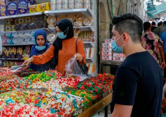 Palestinians, wearing protective facemasks, walk past stores in Jerusalem's Old City on July 3, 2020, during the novel coronavirus pandemic. (Photo by AHMAD GHARABLI / AFP) (Photo by AHMAD GHARABLI/AFP via Getty Images)