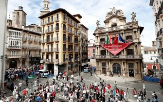 epa08530490 People, many of them wearing the traditional white-and-red San Fermin attire, gather around noon in front of City Hall – from which hangs a giant banner in the shape of the San Fermin festival's emblematic red kerchiefs, promising 'We Will Experience Them' – in Pamplona, northern Spain, 06 July 2020. Pamplona's idiosyncratic Running of the Bulls, known as the Sanfermines, would have normally kicked off on 06 July with the 'Txupinazo' (an opening ceremony involving the firing of a pyrotechnic rocket from City Hall's main balcony). However, the bull-running festival made world-famous by Ernest Hemingway in his 1926 novel 'The Sun Also Rises' has been canceled this year due to the ongoing pandemic of the COVID-19 disease caused by the SARS-CoV-2 coronavirus.  EPA/JESUS DIGES