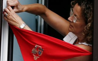 epa08530586 A resident places a red scarf in her window at noon in Pamplona, northern Spain, 06 July 2020. Sanfermines should begin 06 July at noon with a rocket fired from the balcony of the City Hall, but the festival was canceled due to COVID19.  EPA/Jesus Diges
