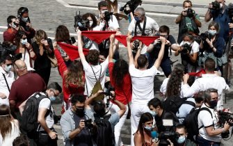 epa08530587 People raise their red scarf as they chant St. Fermin at City Hall' square in Pamplona, northern Spain, 06 July 2020. Sanfermines should begin 06 July at noon with a rocket fired from the balcony of the City Hall, but the festival was canceled due to COVID19.  EPA/Jesus Diges