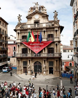 epa08530489 People, many of them wearing the traditional white-and-red San Fermin attire, gather around noon in front of City Hall – from which hangs a giant banner in the shape of the San Fermin festival's emblematic red kerchiefs, promising 'We Will Experience Them' – in Pamplona, northern Spain, 06 July 2020. Pamplona's idiosyncratic Running of the Bulls, known as the Sanfermines, would have normally kicked off on 06 July with the 'Txupinazo' (an opening ceremony involving the firing of a pyrotechnic rocket from City Hall's main balcony). However, the bull-running festival made world-famous by Ernest Hemingway in his 1926 novel 'The Sun Also Rises' has been canceled this year due to the ongoing pandemic of the COVID-19 disease caused by the SARS-CoV-2 coronavirus.  EPA/JESUS DIGES