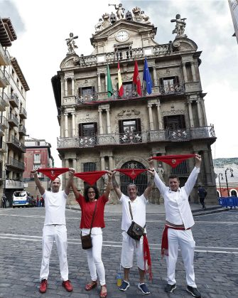 epa08530180 A group of friends wearing the traditional white-and-red San Fermin attire pose for a photograph as they hold up their red kerchiefs in front of City Hall in Pamplona, northern Spain, 06 July 2020. Pamplona's idiosyncratic Running of the Bulls, known as the Sanfermines, would have normally kicked off on 06 July with the 'Txupinazo' (an opening ceremony involving the firing of a pyrotechnic rocket from City Hall's main balcony). However, the bull-running festival made world-famous by Ernest Hemingway in his 1926 novel 'The Sun Also Rises' has been canceled this year due to the ongoing pandemic of the COVID-19 disease caused by the SARS-CoV-2 coronavirus.  EPA/JESUS DIGES